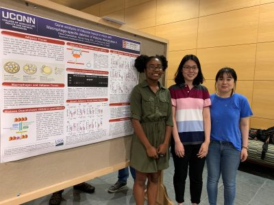 Lab members in front of a bulletin board