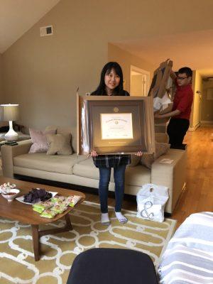 Lab member holding up framed paper award