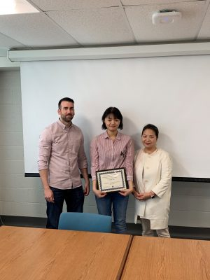 Lab members holding paper award with Professor Lee
