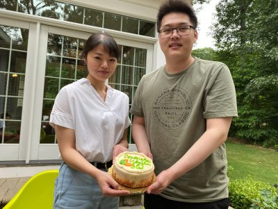 Two lab members holding a cake