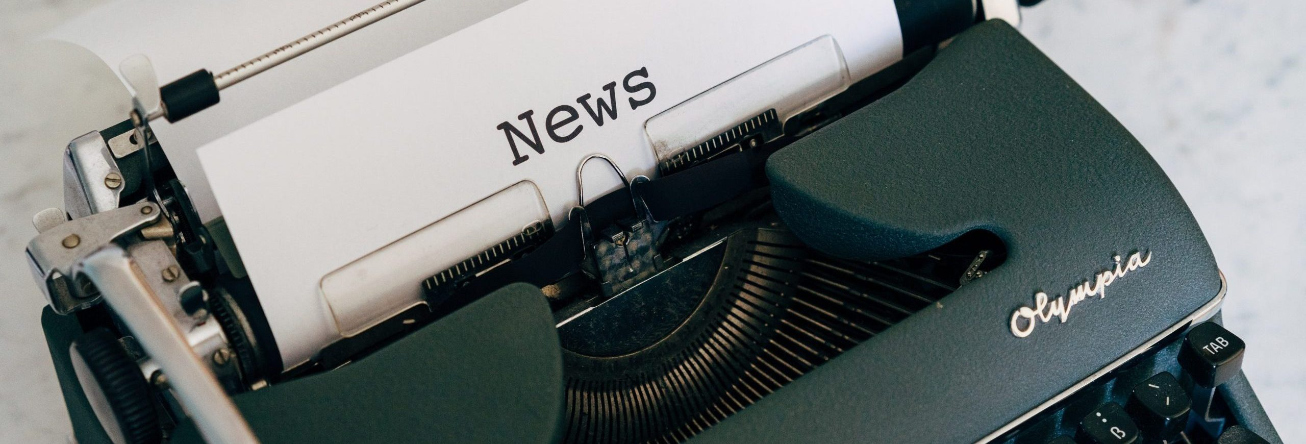 typewriter with paper and word news on it